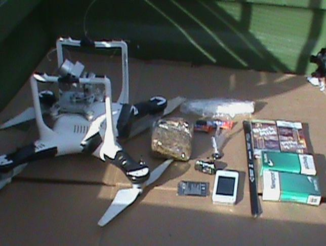 A drone carrying cellphones, drugs, hacksaw blades and other material that dangled in a bundle from a fishing line