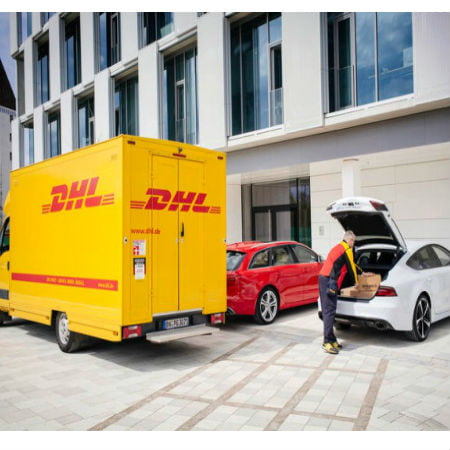 A Yellow Truck and a Delivery Man Putting a Package Into the Rear of the Car