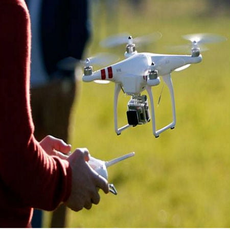 A Person is Holding a Remote Control and a White Drone is Hovering with a Camera Attached on it