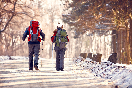 Male and female hikers hiking in winter, back view